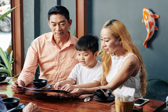 Family reading menu at cafe table - Stock Photo - Images