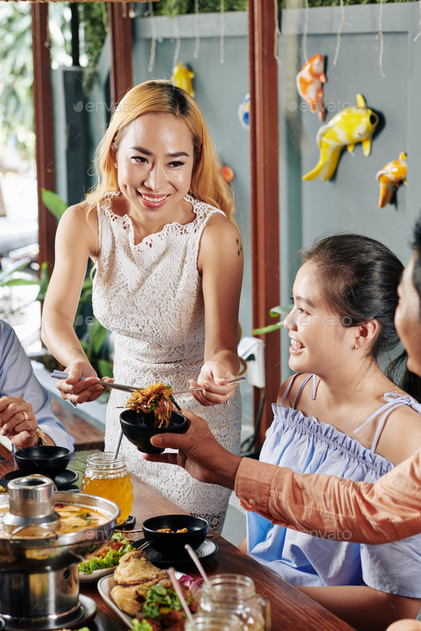Young woman serving food for family - Stock Photo - Images
