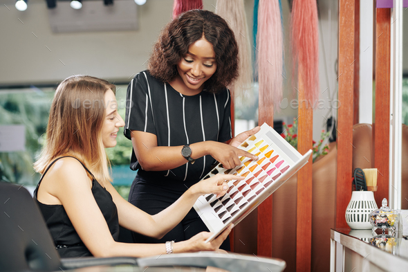 Hairdresser helping client to choose new hair color - Stock Photo - Images