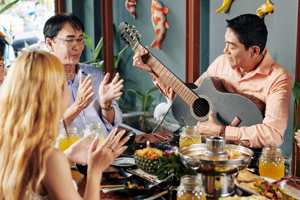 People clapping to friend playing guitar - Stock Photo - Images