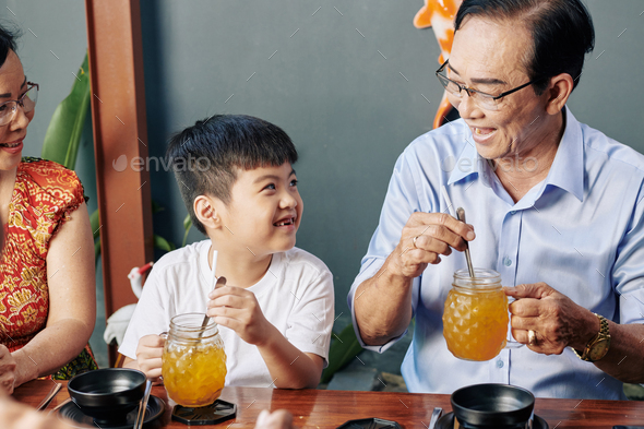 Boy resting in cafe with grandparents - Stock Photo - Images