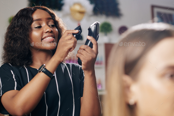 Hairdresser changing head of electric razor - Stock Photo - Images