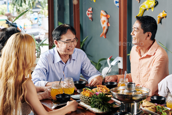 Cheerful family eating dinner in restaurant - Stock Photo - Images