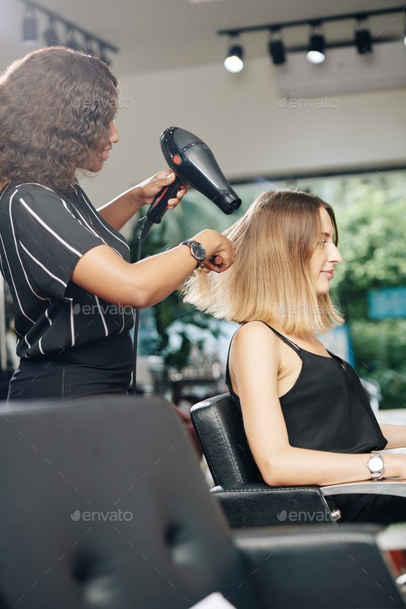 Stylist blowdrying hair of client - Stock Photo - Images
