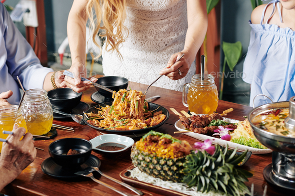 Housewife serving food at dinner - Stock Photo - Images