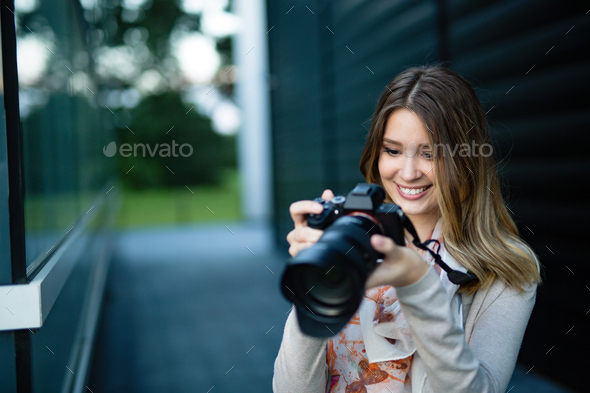 Attractive happy young freelancer woman talking pictures outdoors - Stock Photo - Images