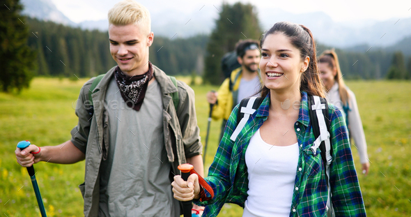 Gorup of friends climbing up hill, with backpacks and climbing stick - Stock Photo - Images