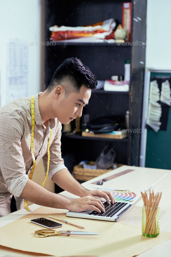 Designer working at laptop at studio - Stock Photo - Images