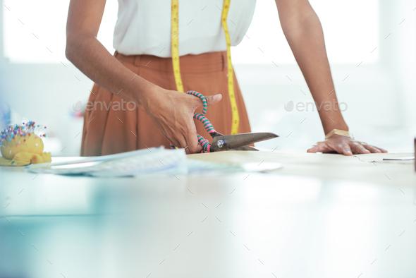 Designer cutting fabric with scissors - Stock Photo - Images