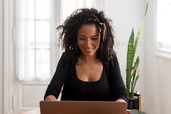 Latin woman working at home with laptop and documents - Stock Photo - Images
