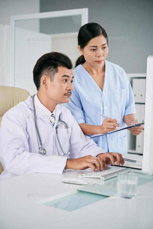 Medical workers checking data on computer - Stock Photo - Images