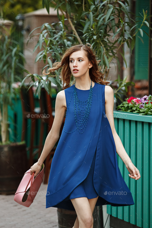 Slim beautiful girl dressed in a blue summer dress holding a pink bag is walking in a city street on - Stock Photo - Images