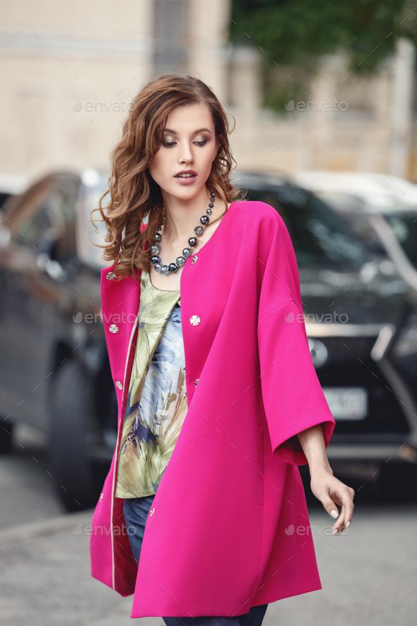 Slim beautiful girl dressed in a stylish summer fuchsia corol coat walks on a city street - Stock Photo - Images
