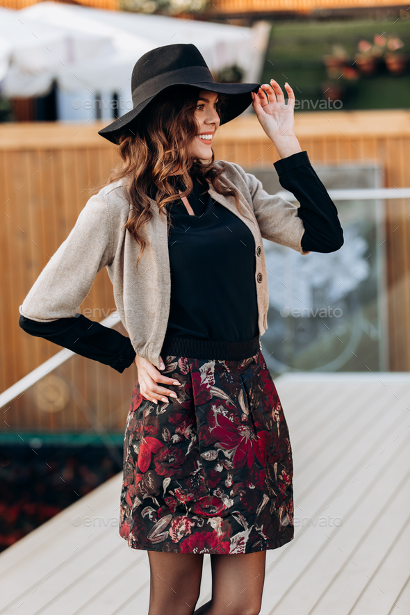 Stylish girl dressed in a black turtleneck, beige cape, stylish short skirt and black hat with wide - Stock Photo - Images