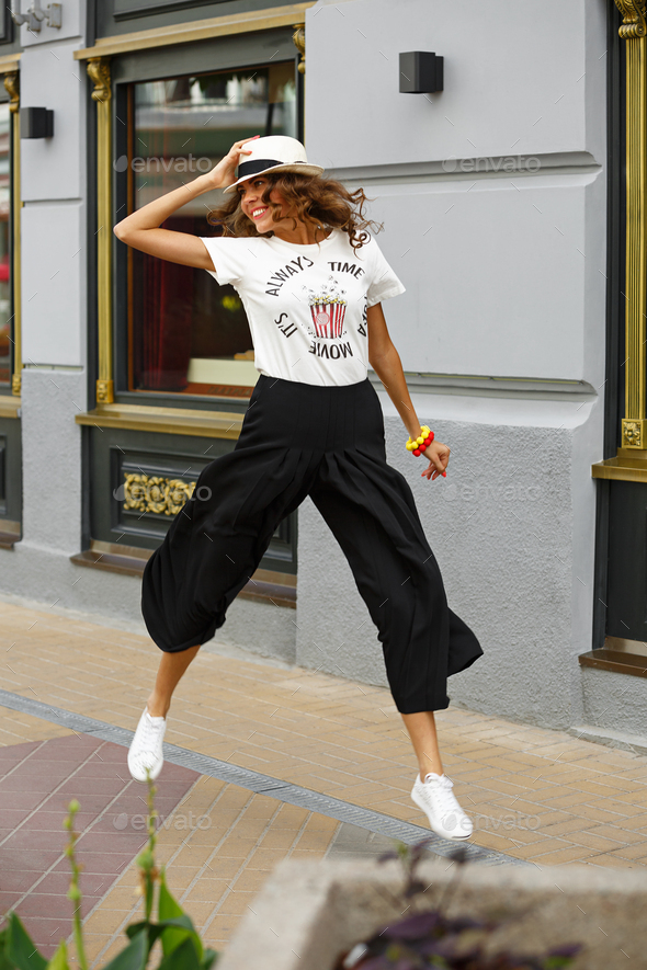 Stylish young girl dressed in a white t-shirt, black wide trousers and white sneakers is jumping in - Stock Photo - Images