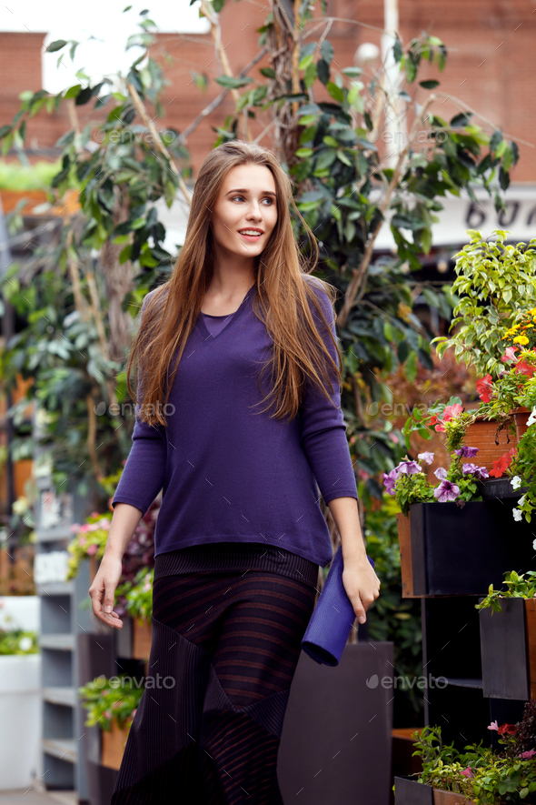 Fashionable girl dressed in a purple sweater and a stylish dark long skirt walks in the park - Stock Photo - Images