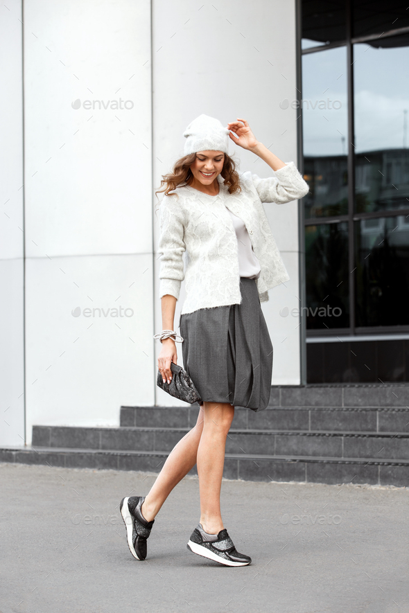 Stylish girl dressed in the fashionable gray skirt, white blouse, white hat and sneakers poses in - Stock Photo - Images