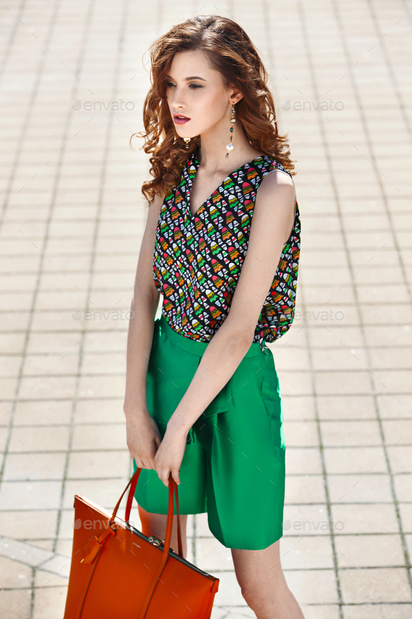 Beautiful women dressed in stylish green shorts and a bright top holding orange bag is walking in - Stock Photo - Images