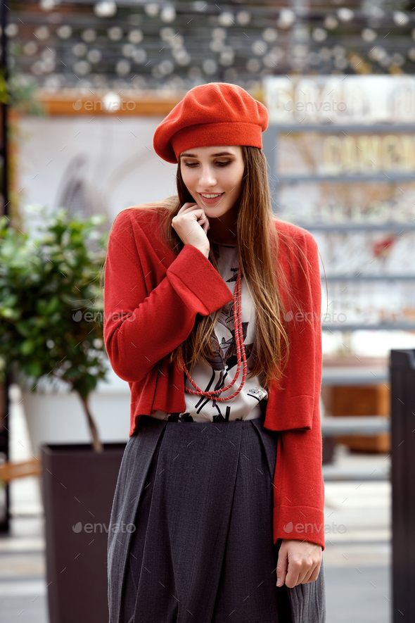 Fashionable girl dressed in a gray skirt, a red blouse on the t-shirt and red beret poses in the - Stock Photo - Images