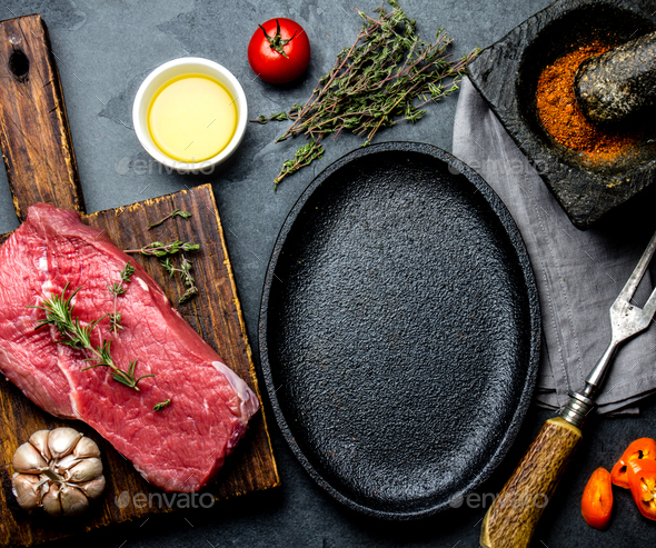 Raw fresh meat steak beef tenderloin, herbs and spices around frying pan plate. - Stock Photo - Images