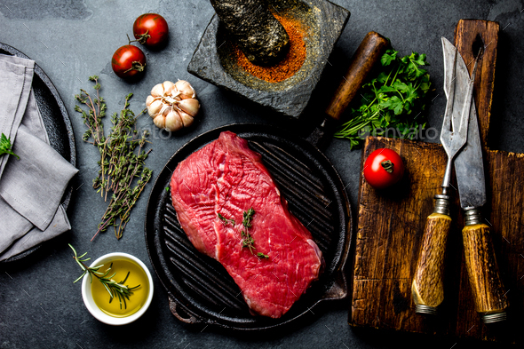Fresh raw meat steak beef tenderloin, herbs and spices around cutting board. - Stock Photo - Images