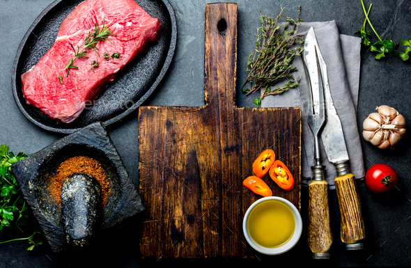 Fresh raw meat steak beef tenderloin, herbs and spices around cutting board - Stock Photo - Images
