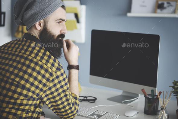 Pensive man at computer desk - Stock Photo - Images