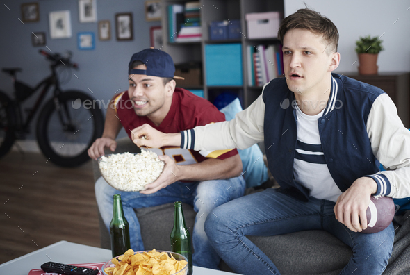 Shot of two excited men in the living room - Stock Photo - Images
