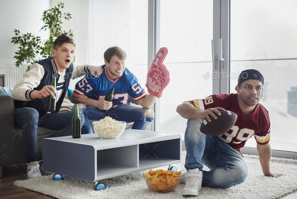 American football fans in front of tv - Stock Photo - Images