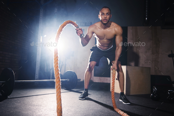 Motivated man throwing ropes at healthy club - Stock Photo - Images
