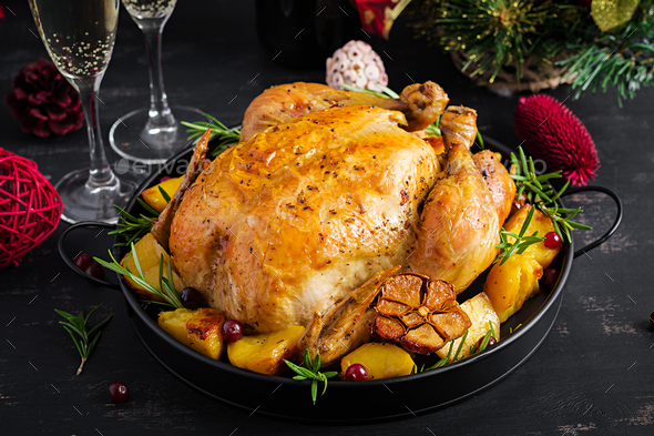 he Christmas table is served with a turkey, decorated with bright tinsel. - Stock Photo - Images