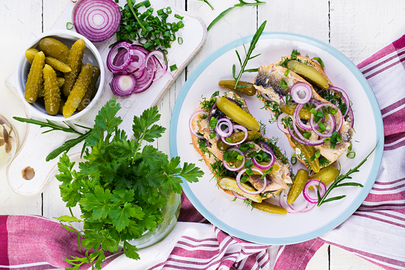 Traditional Dutch sandwich with herring and pickles cucumbers on white table. Smorrebrod.Top view - Stock Photo - Images