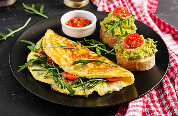 Omelette with tomatoes, cheese, green arugula and toasts with avocado cream on black plate. - Stock Photo - Images