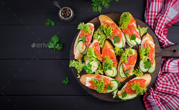 Tapas.  Salted Salmon, butter and cucumber toast sandwiches on wooden board. Top view - Stock Photo - Images