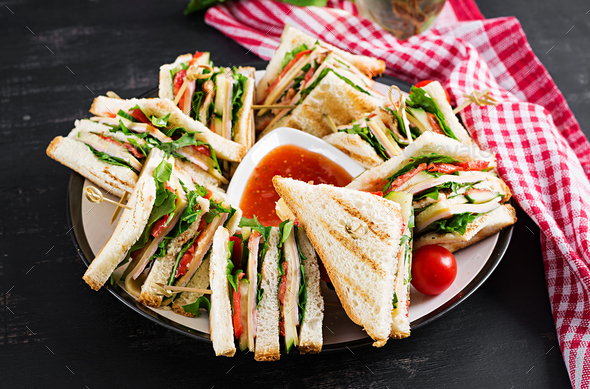 Club sandwich with ham, tomato, cucumber, cheese,  and arugula o - Stock Photo - Images