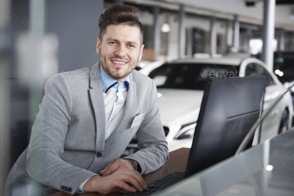 Portrait of salesman leaning at computer desk - Stock Photo - Images