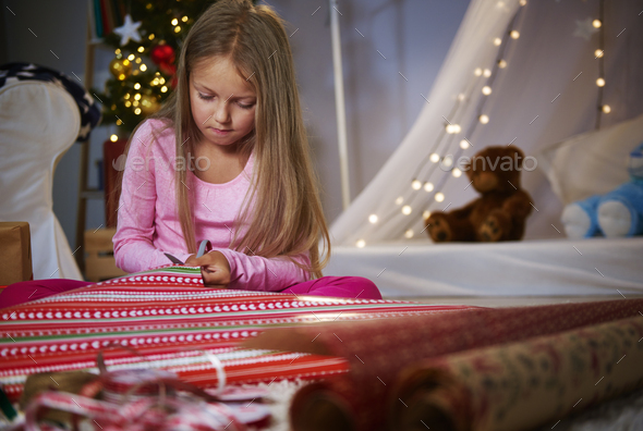 Cute girl cutting a Wrapping paper - Stock Photo - Images