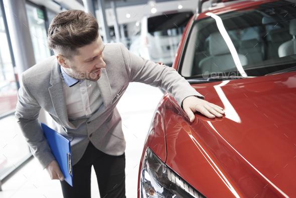 Car salesman examining vehicle before selling - Stock Photo - Images