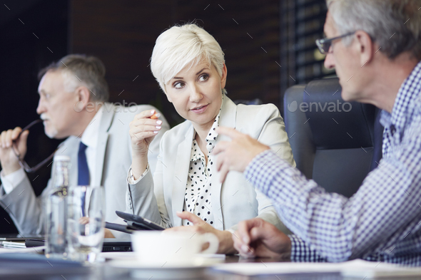 Group of business people huddled around table working - Stock Photo - Images