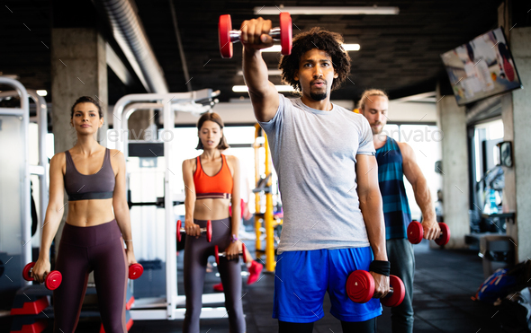 Healthy young athletes friends doing exercises at gym - Stock Photo - Images