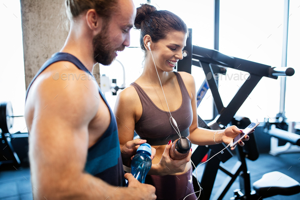 Young sporty woman showing something on smart phone to her male friend in a gym - Stock Photo - Images