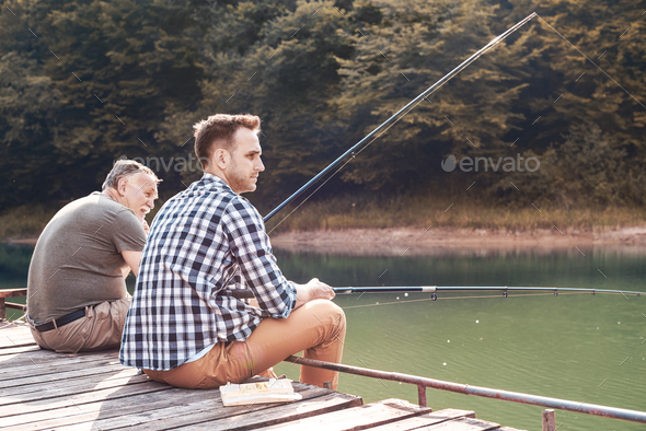 Father with son fishing on jetty - Stock Photo - Images