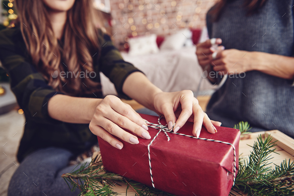 Human hand tying a string on christmas present - Stock Photo - Images