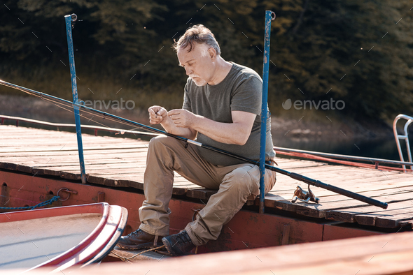 Senior man preparing his fishing rod - Stock Photo - Images