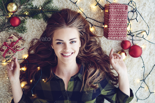 Woman wrapped in christmas lights lying on floor - Stock Photo - Images