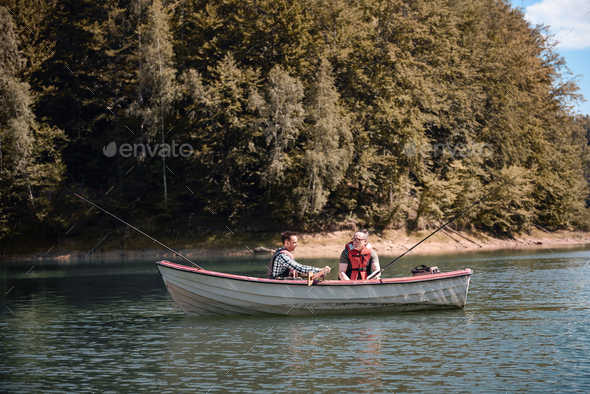 Men fishing in a calm lake from boat - Stock Photo - Images