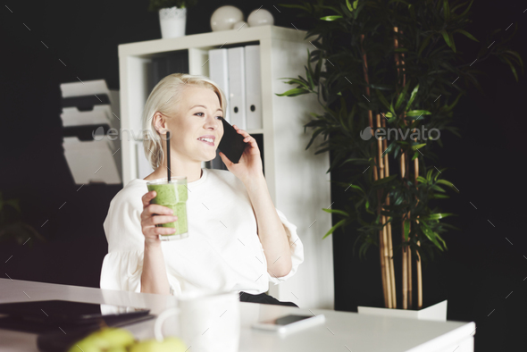 Woman with smoothie have a conversation by phone - Stock Photo - Images