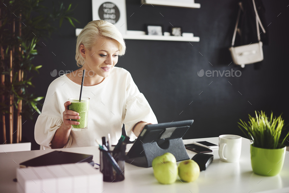 Woman with smoothie using a digital tablet at her desk - Stock Photo - Images