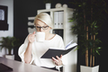 Woman reading book and drinking coffee at her desk - PhotoDune Item for Sale