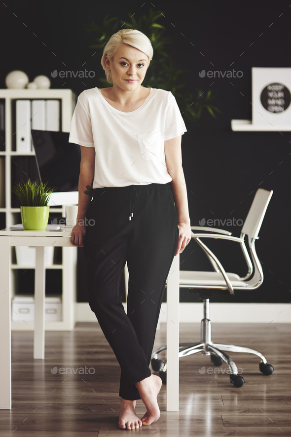 Full-length portrait of barefoot businesswoman leaning against desk - Stock Photo - Images